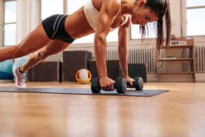 44400056 - strong young woman doing push ups exercise with dumbbells on yoga mat. fitness model doing intense training in the gym.